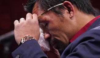 Manny Pacquiao, of the Philippines, wipes his eye at a news conference after his loss to Yordenis Ugas, of Cuba, in a welterweight championship boxing match Saturday, Aug. 21, 2021, in Las Vegas. (AP Photo/John Locher) **FILE**