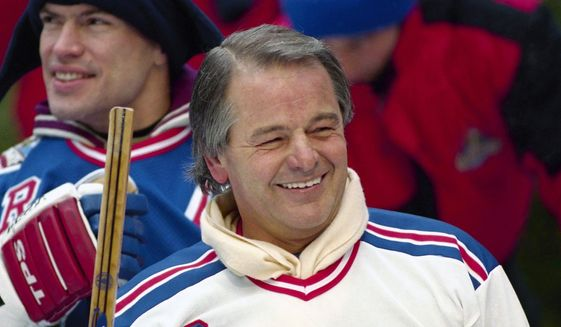 In this Jan. 20, 1994, file photo, former New York Rangers player Rod Gilbert, foreground, and team captain Mark Messier attend a hockey clinic at the skating rink at Rockefeller Center in New York. Gilbert, the Hall of Fame right wing who starred for the Rangers and helped Canada win the 1972 Summit Series, had died. He was 80. Gilbert's family confirmed the death to Rangers on Sunday, Aug. 22, 2021. (AP Photo/Mark Lennihan, File)