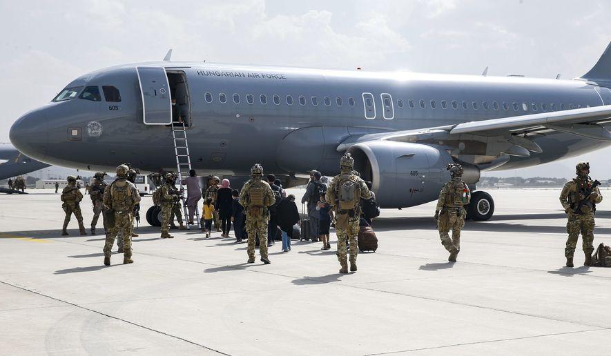 Coalition forces escort evacuees to a plane at Hamid Karzai International Airport, in Kabul Afghanistan. (Lance Cpl. Nicholas Guevara/U.S. Marine Corps via AP)