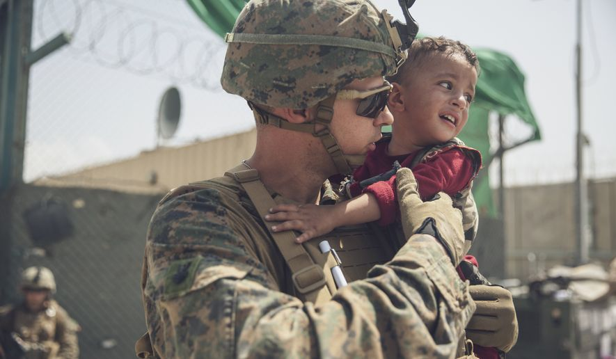 In this Aug. 22, 2021, photo provided by the U.S. Marines, a Marine with the 24th Marine Expeditionary Unit calms a crying toddler during an evacuation at Hamid Karzai International Airport in Kabul Afghanistan. (Staff Sgt. Victor Mancilla/U.S. Marine Corps via AP)