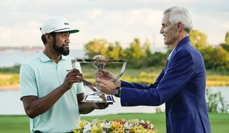 Chairman, President and Chief Executive Officer of Northern Trust Michael G. O'Grady presents the Wanamaker Trophy to Tony Finau after he won at The Northern Trust golf tournament at Liberty National Golf Course Monday, Aug. 23, 2021, in Jersey City, N.J. (AP Photo/John Minchillo)