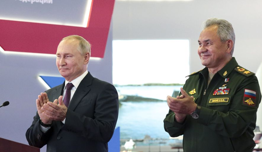 Russian President Vladimir Putin, left, and Russian Defense Minister Sergei Shoigu applaud during the launching of construction of new nuclear submarines and other warships via video conference on the side of the International Military Technical Forum Army-2021 in Alabino, outside Moscow, Russia, Monday, Aug. 23, 2021. Putin has launched the construction of new nuclear submarines and other warships, part of a sweeping military modernization effort amid tensions with the West. He gave orders for two nuclear submarines armed with intercontinental ballistic missiles along with two diesel-powered submarines and two corvettes at shipyards in Severodvinsk, St. Petersburg and Komsomolsk-on-Amur. (Mikhail Klimentyev, Sputnik, Kremlin Pool Photo via AP)
