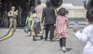 In this image provided by the U.S. Marine Corps, families board a U.S. Air Force Boeing C-17 Globemaster III during an evacuation at Hamid Karzai International Airport in Kabul, Afghanistan, Monday, Aug. 23, 2021. (Sgt. Samuel Ruiz/U.S. Marine Corps via AP)