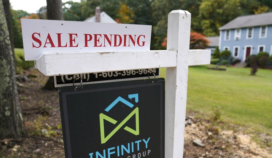 In this Sept. 29, 2020, file photo, a sale pending sign is displayed outside a residential home for sale in East Derry, N.H. Sales of previously occupied U.S. homes rose in July for the second month in a row, though they only increased modestly from a year ago, suggesting the red-hot housing market may be cooling off a little. Existing homes sales rose 2% last month from June to a seasonally-adjusted annual rate of 5.99 million units, the National Association of Realtors said Monday, Aug. 23, 2021. (AP Photo/Charles Krupa, File)