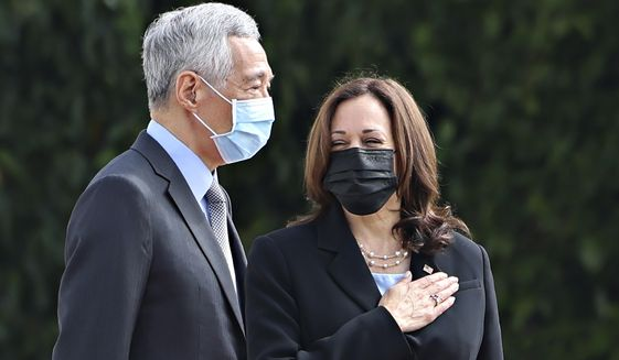 U.S. Vice President Kamala Harris, right, stands next to Singapore's Prime Minister Lee Hsien Loong during a welcome ceremony at the Istana in Singapore Monday, Aug. 23, 2021. (Evelyn Hockstein/Pool Photo via AP)