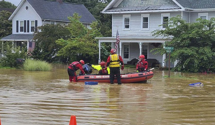 In this photo provided by Mayor Chris Slavicek, emergency personnel and first responders work to help residents after heavy rains from Henri flooded the area, Sunday, Aug. 22, 2021, in Helmetta, N.J. (Chris Slavicek via AP)