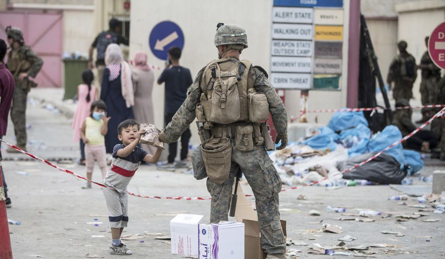 In this Aug. 20, 2021, photo provided by the U.S. Marine Corps, a Marine with the 24th Marine Expeditionary Unit (MEU) provides a meal ready-to-eat to a child during an evacuation at Hamid Karzai International Airport in Kabul, Afghanistan. (Sgt. Samuel Ruiz/U.S. Marine Corps via AP)