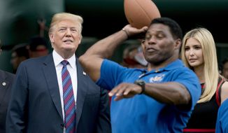 FILE - In this May 29, 2018, file photo, President Donald Trump, left, and his daughter Ivanka Trump, right, watch as former football player Herschel Walker, center, throws a football during White House Sports and Fitness Day on the South Lawn of the White House in Washington. Walker registered to vote on Tuesday, Aug. 17, 2021, in Georgia as Donald Trump has been urging the former football great to join the U.S. Senate in the state as a Republican. (AP Photo/Andrew Harnik, File)
