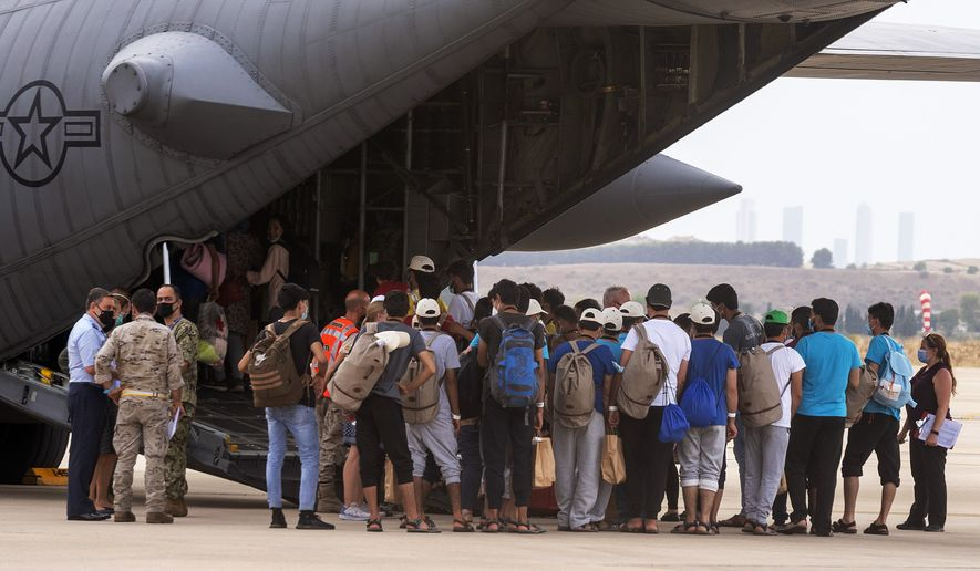Afghan people who were transported from Afghanistan to Madrid, embark on an U.S. military airplane that will transport them to Germany, at the Torrejon military base as part of the evacuation process in Madrid, Spain, Tuesday, Aug. 24, 2021. (AP Photo/Andrea Comas)