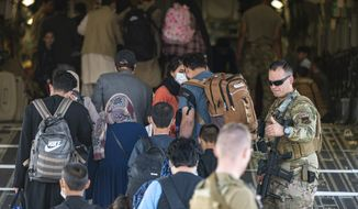 In this image provided by the U.S. Air Force, U.S. Air Force airmen guide evacuees aboard a U.S. Air Force C-17 Globemaster III at Hamid Karzai International Airport in Kabul, Afghanistan, Tuesday, Aug. 24, 2021. (Senior Airman Taylor Crul/U.S. Air Force via AP)