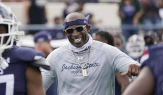 Jackson State football coach Deion Sanders smiles as he greets his defensive squad after they had recovered a Mississippi Valley State fumble for a touchdown during the second half of an NCAA college football game, Sunday, March 14, 2021, in Jackson, Miss. Sanders is trying to win games at Jackson State and raise the profile of historically black colleges and universities around the nation. He's off to a solid first step on the field with a 4-3 mark in the spring. This fall will be the real test. His team opens with Florida A&M on Sept. 5 in the Orange Blossom Classic. It's one of eight games on Jackson State's schedule that will be televised on an ESPN network. (AP Photo/Rogelio V. Solis) **FILE**