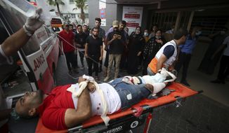 Medics move Osama Dueij, 32, who was shot in the leg by Israeli troops during a violent protest at the Gaza Strip's border with Israel, into the treatment room of Shifa hospital in Gaza City, Saturday, Aug. 21, 2021. (AP Photo/Abdel Kareem Hana)