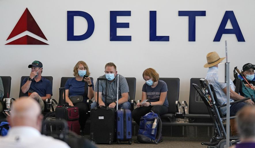 People sit under a Delta sign at Salt Lake City International Airport on July 1, 2021, in Salt Lake City. Delta Air Lines won't force employees to get vaccinated, but it's going to make unvaccinated workers pay a $200 monthly charge. Delta said Wednesday, Aug. 25, 2021 that it will also require weekly testing for unvaccinated employees starting next month, although the airline says it'll pick up the cost of that testing. (AP Photo/Rick Bowmer, File)