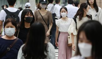 People wearing face masks to help protect against the spread of the coronavirus walk across an intersection Tuesday, Aug. 24, 2021. (AP Photo/Koji Sasahara)