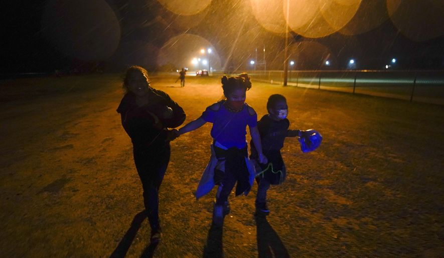 In this May 11, 2021, file photo, three young migrants hold hands as they run in the rain at an intake area after turning themselves in upon crossing the U.S.-Mexico border in Roma, Texas. Five months after the Biden administration declared an emergency and raced to set up shelters to house a record number of children crossing the U.S.-Mexico border alone, kids continue to languish at the sites, while more keep coming, child welfare advocates say. (AP Photo/Gregory Bull) ** FILE **