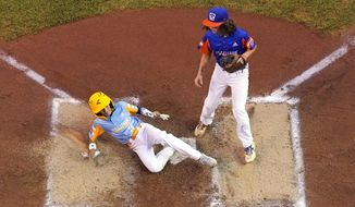 Honolulu's Kaikea Patoc-Young (9) scores on a wild pitch by Taylor, Mich.'s Ethan Van Belle, right, during the first inning of a baseball game at the Little League World Series in South Williamsport, Pa., Wednesday, Aug. 25, 2021. Hawaii won 2-0. (AP Photo/Gene J. Puskar) **FILE**