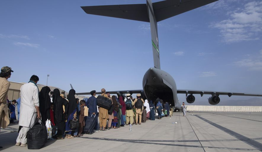In this image provided by the U.S. Air Force, U.S. Air Force loadmasters and pilots assigned to the 816th Expeditionary Airlift Squadron, load people being evacuated from Afghanistan onto a U.S. Air Force C-17 Globemaster III at Hamid Karzai International Airport in Kabul, Afghanistan, Tuesday, Aug. 24, 2021. (Master Sgt. Donald R. Allen/U.S. Air Force via AP)  **FILE**