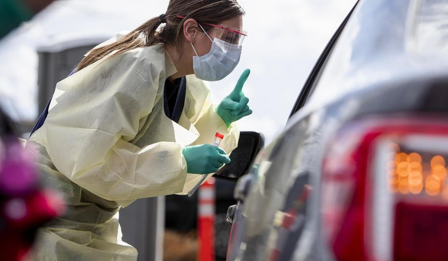 """FILE - In this March 17, 2020 file photo, Ashley Layton, an LPN at St. Luke's Meridian Medical Center, communicates with a person before taking swab sample at a special outdoor drive-thru screening station for COVID-19 in Meridian, Idaho. Hospital facilities and public health agencies are scrambling to add capacity however they can as the number of coronavirus cases continue to rise statewide. On Thursday, Aug. 26, 2021, some Idaho hospitals only narrowly avoided enacting """"crisis standards of care,"""" where scarce healthcare resources are allotted to the patients most likely to benefit, thanks in part to statewide coordination. (Darin Oswald/Idaho Statesman via AP, File)"""