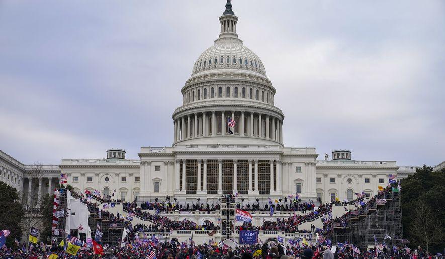 In this Jan. 6, 2021, file photo demonstrators loyal to President Donald Trump riot outside the Capitol in Washington.  (AP Photo/John Minchillo, File)  **FILE**