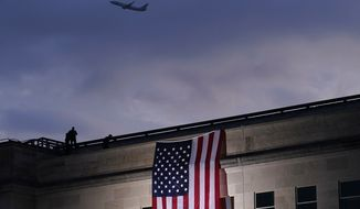 In this Friday, Sept. 11, 2020, file photo, a plane takes off from Washington Reagan National Airport as a large U.S. flag is unfurled at the Pentagon ahead of ceremonies at the National 9/11 Pentagon Memorial to honor the 184 people killed in the 2001 terrorist attack on the Pentagon, in Washington, Friday, Sept. 11, 2020. (AP Photo/J. Scott Applewhite, File)  ** FILE **