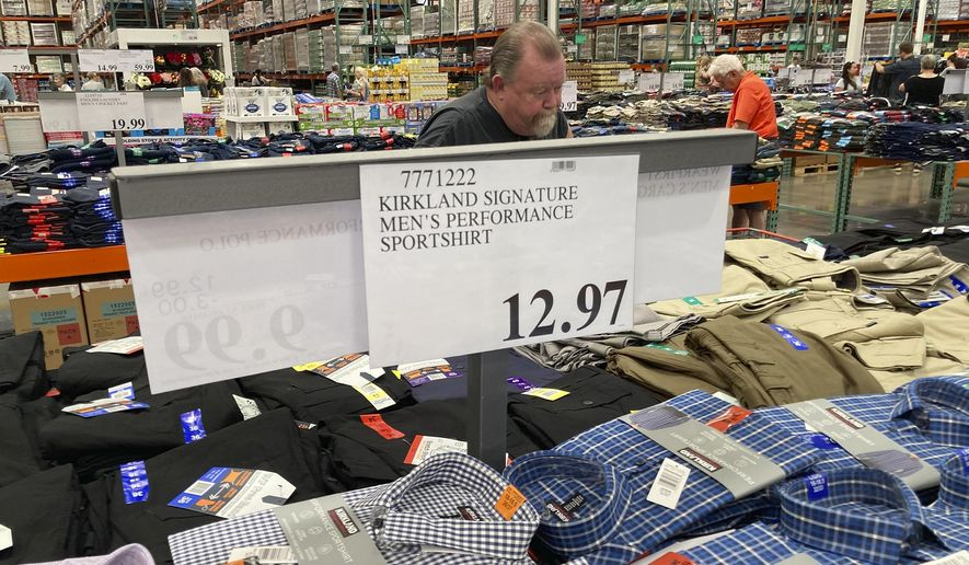 A sign displays the price for shirts as a shopper peruses the offerings at a Costco warehouse in this photograph taken Thursday, June 17, 2021, in Lone Tree, Colo.  Growth in U.S. consumer spending slowed in July to a modest increase of 0.3% while inflation over the past 12 months rose to the fastest pace in three decades. (AP Photo/David Zalubowski) ** FILE **