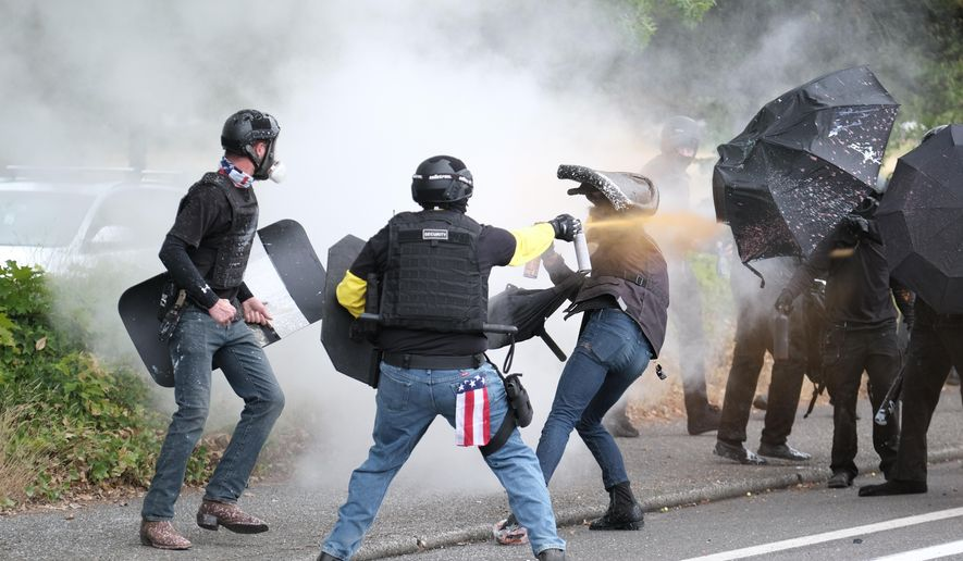 This Sunday, Aug. 22, 2021, file photo, members of the far-right group Proud Boys and anti-fascist protesters spray bear mace at each other during clashes between the politically opposed groups in Portland, Ore.  Police in Portland have been criticized that they did little to prevent violent clashes between right- and left-wing protesters on Sunday.  (AP Photo/Alex Milan Tracy)