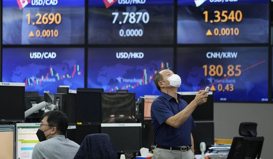 A currency trader uses a remote control to adjust temperature on an overhead air-conditioner at the foreign exchange dealing room of the KEB Hana Bank headquarters in Seoul, South Korea, Friday, Aug. 27, 2021. Asian stock markets were mixed Friday as investors awaited more guidance on the U.S. Federal Reserve's easing plans. (AP Photo/Ahn Young-joon)