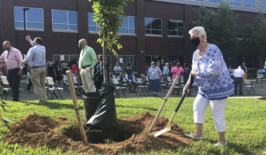 Deborah D. Petit, former superintendent of Louisa County Public Schools, shovels dirt onto a newly planted tree meant to commemorate the community's efforts in the wake of the 2011 earthquake in Mineral, Va.,/The Daily Progress via AP)