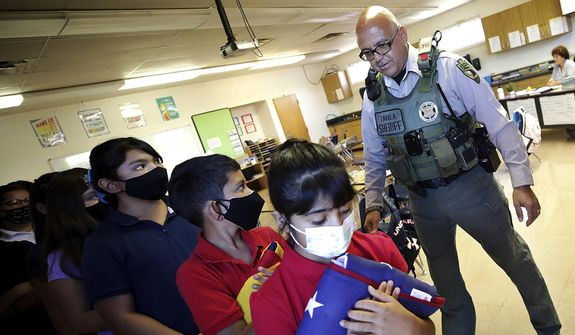 Cochise County Sheriff's Deputy Bobby Zavala gathers Naco Elementary School fifth graders for the daily raising of the American and state flags, Thursday, Aug. 19, 2021, in Naco, Ariz. Zavala, the school's first resource officer, has many duties he performs throughout the day at this unique place of learning, located about 700 yards from the U.S.-Mexico border. (Mark Levy/Sierra Vista Herald via AP) **FILE**
