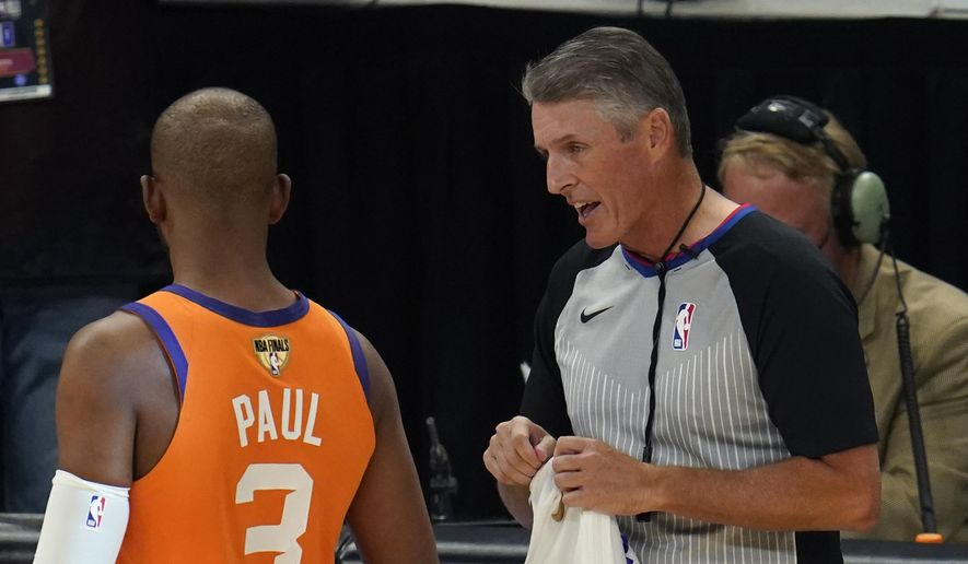 In this Tuesday, July 20, 2021, file photo, referee Scott Foster talks with Phoenix Suns guard Chris Paul (3) before the start of Game 6 of basketball's NBA Finals against the Milwaukee Bucks in Milwaukee. The NBA said Saturday, Aug. 28, 2021, that its referees have all agreed to be vaccinated as a condition for working games this season. (AP Photo/Paul Sancya, File) **FILE**