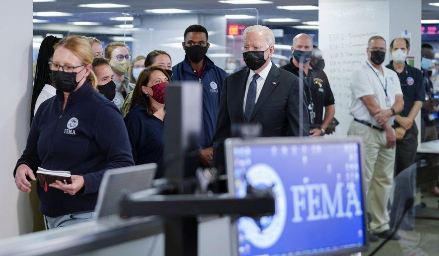 President Joe Biden arrives at theNational Response Coordination Center at FEMA headquarters, Sunday, Aug. 29, 2021, in Washington. FEMA Administrator Deanne Criswell is at left. (AP Photo/Manuel Balce Ceneta)