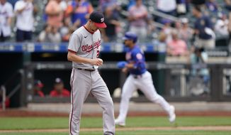 Washington Nationals starting pitcher Erick Fedde, foreground, reacts to New York Mets' Javier Baez's two-run home run, also scoring Michael Conforto, during the fourth inning of a baseball game, Sunday, Aug. 29, 2021, in New York. (AP Photo/Corey Sipkin)