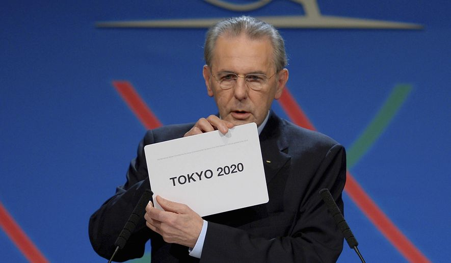 In this Saturday, Sept. 7, 2013 file photo, International Olympic Committee (IOC) President Jacques Rogge shows the name of the city of Tokyo elected to host the 2020 Summer Olympics in Buenos Aires, Argentina. The International Olympic Committee on Sunday, Aug, 29, 2021 says Jacques Rogge who led the organization as president for 12 years, has died. He was 79. (Fabrice Coffrini/Pool photo via AP, file) **FILE**