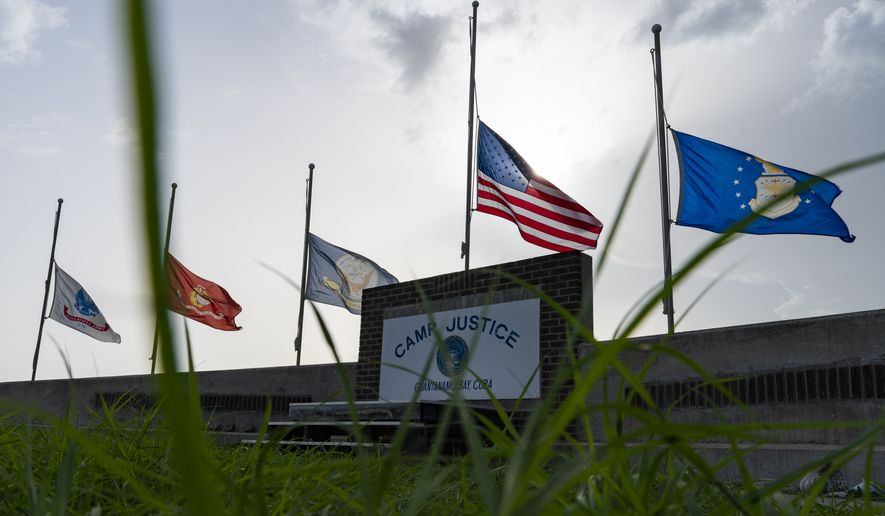In this photo reviewed by U.S. military officials, flags fly at half-staff in honor of the U.S. service members and other victims killed in the terrorist attack in Kabul, Afghanistan, at Camp Justice, Sunday, Aug. 29, 2021, in Guantanamo Bay Naval Base, Cuba. Camp Justice is where the military commission proceedings are held for detainees charged with war crimes. (AP Photo/Alex Brandon)