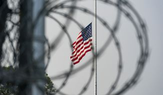 In this photo reviewed by U.S. military officials, a flag flies at half-staff in honor of the U.S. service members and other victims killed in the terrorist attack in Kabul, Afghanistan, as seen through a fence at Camp Justice, Sunday, Aug. 29, 2021, in Guantanamo Bay Naval Base, Cuba. Camp Justice is where the military commission proceedings are held for detainees charged with war crimes. (AP Photo/Alex Brandon)