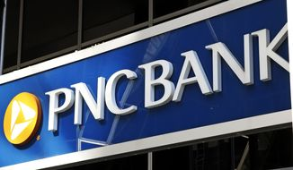 This is the sign on a PNC Bank branch in downtown Pittsburgh, Sunday, May 31, 2020. PNC Bank is the latest large U.S. financial services company to increase wages in a bid to keep and attract employees. It is raising its minimum wage to $18 an hour while also giving higher-paid workers a bump in pay. The bank said Monday, Aug. 30, 2021, that the wage increase will apply to both PNC employees as well as those working for BBVA USA, which PNC acquired last year. (AP Photo/Gene J. Puskar) ** FILE **