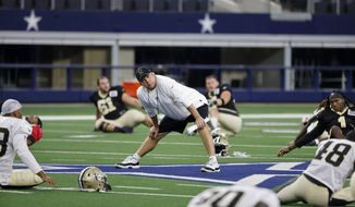 New Orleans Saints head coach Sean Payton, center, stands on the field as his team stretches as they prepare for an NFL football workout in Arlington, Texas, Monday, Aug. 30, 2021. Displaced by Hurricane Ida, the Saints went back to work Monday about 500 miles away in the home of another NFL team. (AP Photo/Michael Ainsworth)