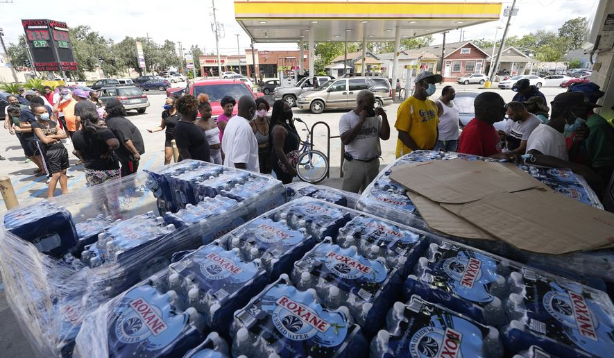 Customers stand in line to shop at a convenience store with no electricity after the effects of Hurricane Ida knocked out power in the area, Monday, Aug. 30, 2021, in New Orleans, La. (AP Photo/Eric Gay)