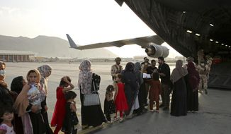 Afghans prepare to to be evacuated aboard a Qatari transport plane, at Hamid Karzai International Airport in Kabul, Afghanistan, August, 18, 2021. Qatar played an out-sized role in U.S. efforts to evacuate tens of thousands of people from Afghanistan. Now the tiny Gulf Arab state is being asked to help shape what is next for Afghanistan because of its ties with both Washington and the Taliban insurgents now in charge in Kabul. (Qatar Government Communications Office via AP)