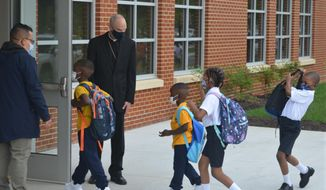 Youngsters enter the first new Catholic school built in Baltimore in roughly 60 years with a mix of enthusiasm and first-day-back jitters, Monday Aug. 30, 2021. The new 65,000 square foot school near downtown Baltimore is an anomaly in the national education landscape where the pandemic has shuttered many parish schools. It's named after Mother Mary Lange, who started a Catholic school for Black children in 1828 _ the first U.S. Catholic school for African-American youth. (AP Photo/David McFadden)