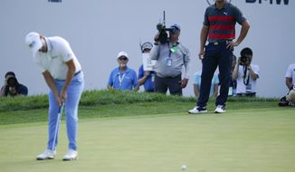 Bryson DeChambeau, right, watches as Patrick Cantlay putts on the 16th green during the final round of the BMW Championship golf tournament, Sunday, Aug. 29, 2021, at Caves Valley Golf Club in Owings Mills, Md. (AP Photo/Julio Cortez) **FILE**