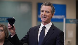 In this July 26, 2021, photo Gov. Gavin Newsom holds a face mask while speaking at a news conference in Oakland, Calif. Conservative radio talk show host Larry Elder has emerged as the top contender for those who are looking to unseat Newsom in the Sept. 14th recall election. Elder, who is running to replace Newsom in the Sept. 14 recall election, says he would erase state vaccine and mask mandates, is critical of gun control, opposes the minimum wage and disputes the notion of systemic racism in America. (AP Photo/Jeff Chiu) **FILE**
