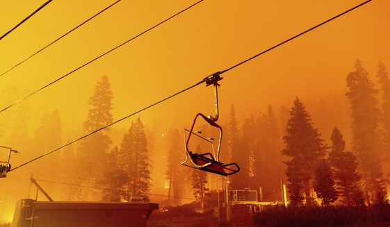 Seen in a long camera exposure, the Caldor Fire burns as a chair lift sits at the Sierra-at-Tahoe ski resort on Sunday, Aug. 29, 2021, in Eldorado National Forest, Calif. The main buildings at the ski slope's base survived as the main fire front passed. (AP Photo/Noah Berger)