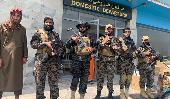 Taliban fighters stand guard inside the Hamid Karzai International Airport after the U.S. withdrawal in Kabul, Afghanistan, Tuesday, Aug. 31, 2021. The Taliban were in full control of Kabul's international airport on Tuesday, after the last U.S. plane left its runway, marking the end of America's longest war. (AP Photo/Kathy Gannon) ** FILE **