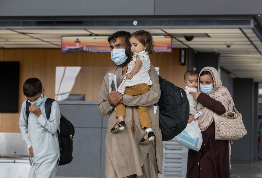 Families evacuated from Kabul, Afghanistan, walk through the terminal to board a bus after they arrived at Washington Dulles International Airport, in Chantilly, Va., on Tuesday, Aug. 31, 2021. (AP Photo/Gemunu Amarasinghe)