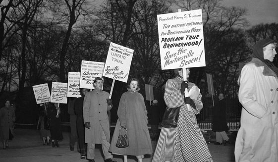 In this Jan. 30, 1951, file photo, as temperatures drop below freezing, demonstrators march in front of the White House in Washington, in what they said was an effort to persuade President Harry Truman to halt the execution of seven Black men sentenced to death in Virginia on charges of raping a white woman. Virginia Gov. Ralph Northam granted posthumous pardons Tuesday, Aug. 31, 2021, to seven Black men who were executed in 1951 for the rape of a white woman, in a case that attracted pleas for mercy from around the world and in recent years has been denounced as an example of racial disparity in the use of the death penalty. (AP Photo/Henry Burroughs, File)