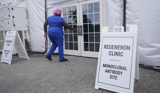 A nurse enters a monoclonal antibody site, Wednesday, Aug. 18, 2021, at C.B. Smith Park in Pembroke Pines, Fla. Numerous sites are open around the state offering monoclonal antibody treatment sold by Regeneron to people who have tested positive for COVID-19. Florida Gov. Ron DeSantis continues to tour the state touting the use of monoclonal antibodies as a treatment for those who get sick with COVID-19 and to relieve pressure on hospitals. (AP Photo/Marta Lavandier)
