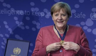 """German Chancellor Angela Merkel, right, smiles after she received a medal by Tedros Adhanom Ghebreyesus, left, director-general of the World Health Organization (WHO), during the inauguration ceremony of the 'WHO Hub For Pandemic And Epidemic Intelligence"""" at the Langenbeck-Virchow building in Berlin, Germany, Wednesday, Sept. 1, 2021. (AP Photo/Michael Sohn, pool)"""
