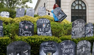 In this Aug. 9, 2021, file photo, Jayde Newton helps to set up cardboard gravestones with the names of victims of opioid abuse outside the courthouse where the Purdue Pharma bankruptcy is taking place in White Plains, N.Y. A federal bankruptcy judge is expected to rule Wednesday, Sept. 1, on whether to accept a settlement between OxyContin maker Purdue Pharma, the states and thousands of local governments over an opioid crisis that has killed a half-million Americans over the last two decades. (AP Photo/Seth Wenig, File)