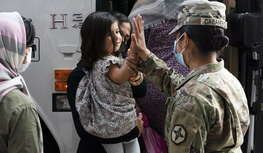 In this Monday, Aug. 30, 2021, file photo, Army Pfc. Kimberly Hernandez gives a high-five to a girl evacuated from Kabul, Afghanistan, before boarding a bus after they arrived at Washington Dulles International Airport, in Chantilly, Va. U.S. religious groups of many faiths are gearing up to assist the thousands of incoming refugees. (AP Photo/Jose Luis Magana, File)